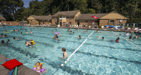 a large outdoor pool filled with people using float toys or swimming